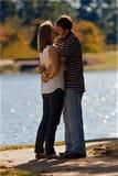 Pares jovenes en beso del amor por un lago Foto de archivo
