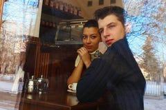 Pares jovenes en café, visión a través de una ventana Imágenes de archivo libres de regalías