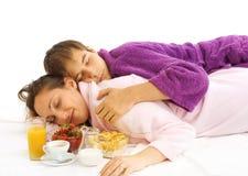 Pares jovenes en cama con el desayuno Imágenes de archivo libres de regalías