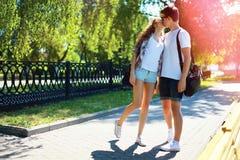 Pares jovenes en caminar que se besa del amor en parque de la ciudad en el verano Foto de archivo