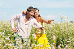 Pares jovenes en campo con las flores frescas Fotografía de archivo