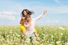 Pares jovenes en campo con las flores frescas Fotos de archivo libres de regalías