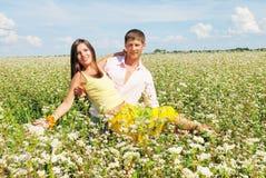 Pares jovenes en campo con las flores frescas Imágenes de archivo libres de regalías