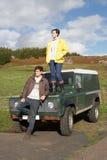 Pares jovenes en campo con SUV Imagen de archivo libre de regalías