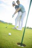 Pares jovenes en campo de golf imagen de archivo libre de regalías