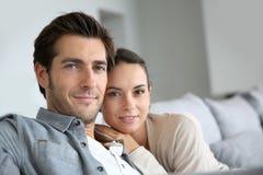 Pares jovenes en casa que se relajan en el sofá Fotos de archivo libres de regalías