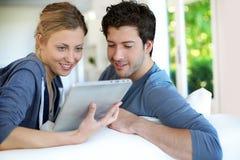 Pares jovenes en casa usando el goce de la tableta Imagen de archivo libre de regalías