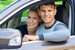 Pares jovenes en coche Imágenes de archivo libres de regalías