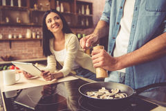 Pares jovenes en cocina fotografía de archivo