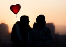 Pares jovenes en corazón del globo del amor Imagenes de archivo