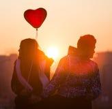 Pares jovenes en corazón del globo del amor Fotos de archivo