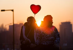 Pares jovenes en corazón del globo del amor Foto de archivo libre de regalías