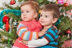 Pares jovenes en el árbol de navidad adornado Fotos de archivo