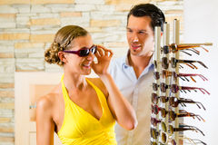 Pares jovenes en el óptico con los vidrios Imágenes de archivo libres de regalías