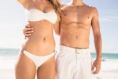 Pares jovenes en el abarcamiento de la ropa de playa Fotos de archivo