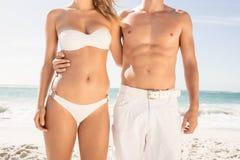 Pares jovenes en el abarcamiento de la ropa de playa Imagenes de archivo