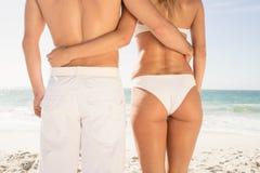 Pares jovenes en el abarcamiento de la ropa de playa Imagen de archivo libre de regalías