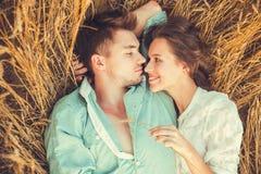 Pares jovenes en el amor al aire libre Junte el abrazo Pares hermosos jovenes en el amor que permanece y que se besa en el campo  Fotos de archivo libres de regalías
