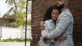 Pares jovenes en el amor que abraza en la calle metrajes