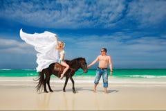 Pares jovenes en el amor que camina con el caballo en una playa tropical Fotos de archivo