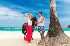 Pares jovenes en el amor que camina con el caballo en una playa tropical Imagenes de archivo