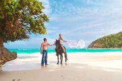 Pares jovenes en el amor que camina con el caballo en una playa tropical Fotografía de archivo