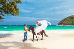 Pares jovenes en el amor que camina con el caballo en una playa tropical Fotos de archivo libres de regalías