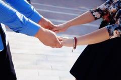 Pares jovenes en el amor que camina en el parque que lleva a cabo las manos Fotos de archivo libres de regalías