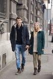 Pares jovenes en el amor que camina en la ciudad Fotos de archivo libres de regalías