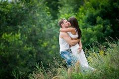 Pares jovenes en el amor que camina en un prado Fotografía de archivo libre de regalías