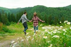 Pares jovenes en el amor que camina en montañas Foto de archivo libre de regalías