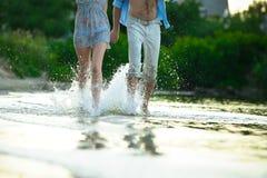 Pares jovenes en el amor que corre a través del agua que lleva a cabo las manos Imagenes de archivo