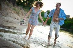 Pares jovenes en el amor que corre a través del agua que lleva a cabo las manos Imagen de archivo