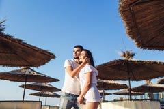 Pares jovenes en el amor que lleva a cabo las manos entre los paraguas de lámina en la playa del mar imagen de archivo libre de regalías