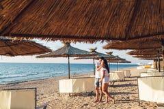 Pares jovenes en el amor que lleva a cabo las manos entre los paraguas de lámina en la playa del mar foto de archivo libre de regalías