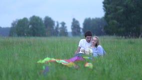 Pares jovenes en el amor que miente en la hierba en el campo, el abrazo y hablar metrajes