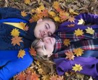 Pares jovenes en el amor que miente en las hojas caidas Imagen de archivo libre de regalías