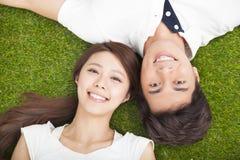 pares jovenes en el amor que miente junto en la hierba Foto de archivo libre de regalías
