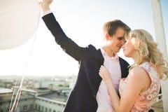 Pares jovenes en el amor que presenta en el tejado con la opinión perfecta de la ciudad que celebra las manos y el abrazo Puesta  Foto de archivo libre de regalías
