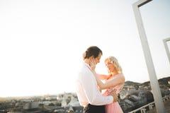 Pares jovenes en el amor que presenta en el tejado con la opinión perfecta de la ciudad que celebra las manos y el abrazo Puesta  Fotografía de archivo
