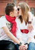 Pares jovenes en el amor que se besa Imagen de archivo libre de regalías