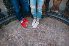 Pares jovenes en el amor que se coloca en la calle en gumshoes en verano Imágenes de archivo libres de regalías