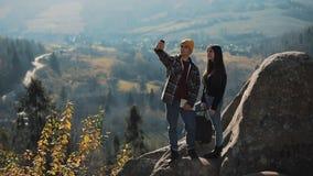 Pares jovenes en el amor que se coloca en las rocas y que toma un retrato del selfie Hombre y mujer que visitan al turista famoso almacen de video