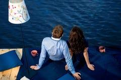 Pares jovenes en el amor que se relaja en terraza cerca del agua Foto de archivo libre de regalías