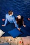 Pares jovenes en el amor que se relaja en terraza cerca del agua Fotografía de archivo