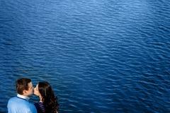 Pares jovenes en el amor que se relaja en terraza cerca del agua Imagen de archivo libre de regalías