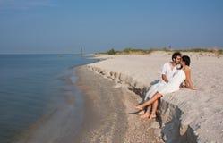 Pares jovenes en el amor que se sienta en la playa Fotografía de archivo