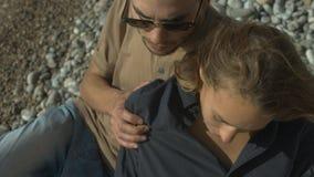 pares jovenes en el amor que se sienta en la playa almacen de metraje de vídeo