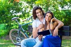 Pares jovenes en el banco de parque Imagen de archivo libre de regalías