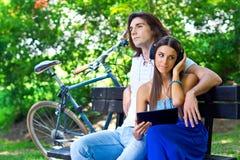 Pares jovenes en el banco de parque Foto de archivo libre de regalías